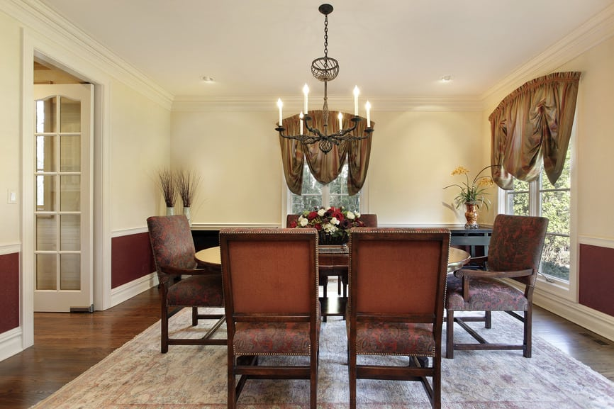 A spacious dining room boasting an oval dining table set on top of an area rug covering the hardwood flooring. The room features a candlelight chandelier.