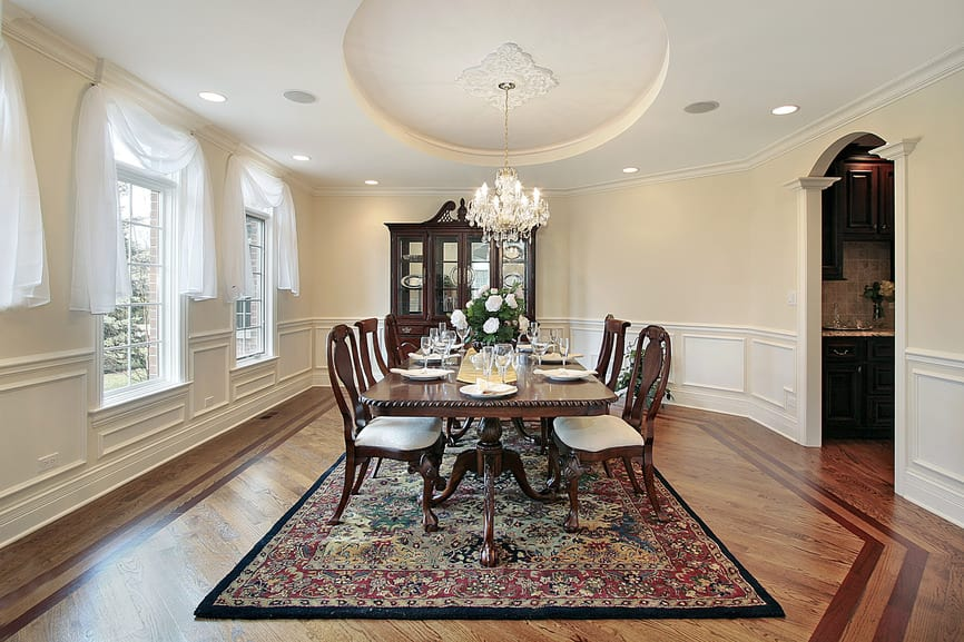 A large dining room boasting a gorgeous tray ceiling and decorated hardwood flooring topped by an area rug where the classy dining table set is situated.