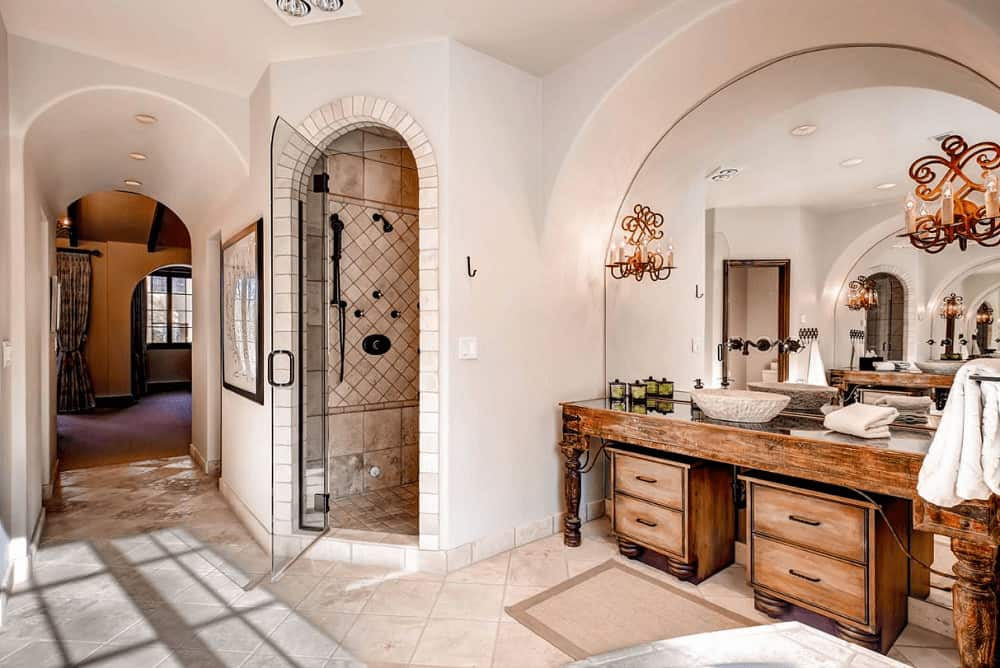 This primary bathroom showcases a walk-in shower and natural wood vessel sink vanity with an arched mirror mounted with beautiful candle sconces.