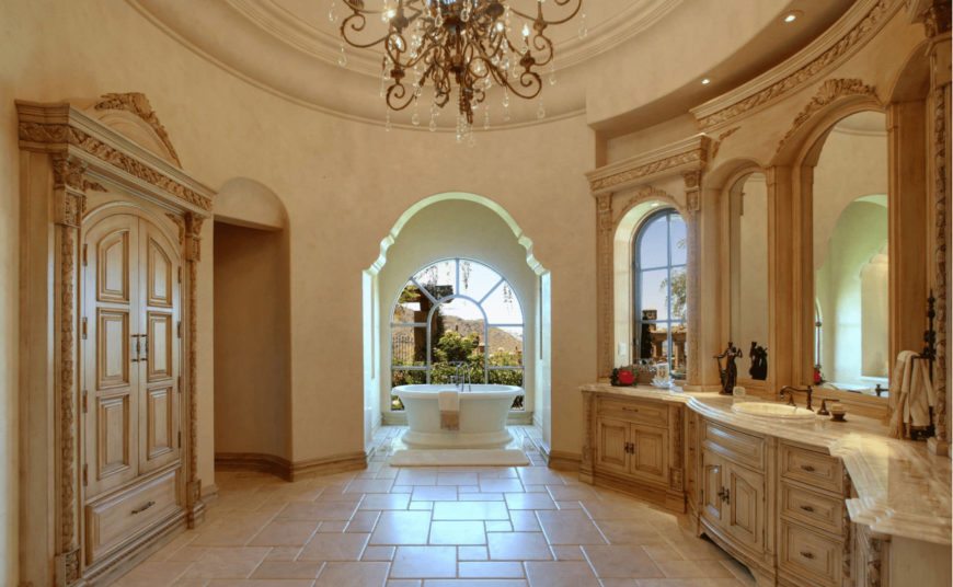 Mediterranean primary bathroom with a glamorous chandelier and wooden sink vanity that complements the built-in wardrobe. It includes a freestanding tub by the arched window overlooking the outdoor scenery.