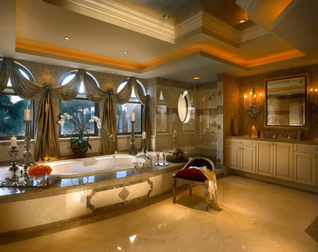 Deluxe primary bathroom with marble tiled flooring and arched windows dressed in classy curtains. It includes a walk-in shower and drop-in tub paired with a red cushioned chair.