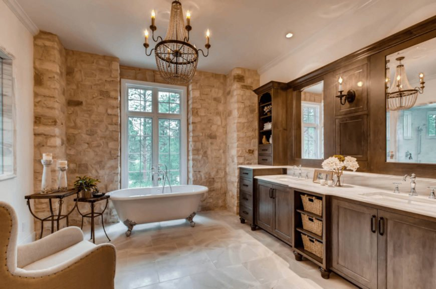 A stone brick wall adds texture in this primary bathroom with a cozy seat and clawfoot tub lighted by an oversized chandelier. It includes natural wood vanity with white marble countertop and dual sink.