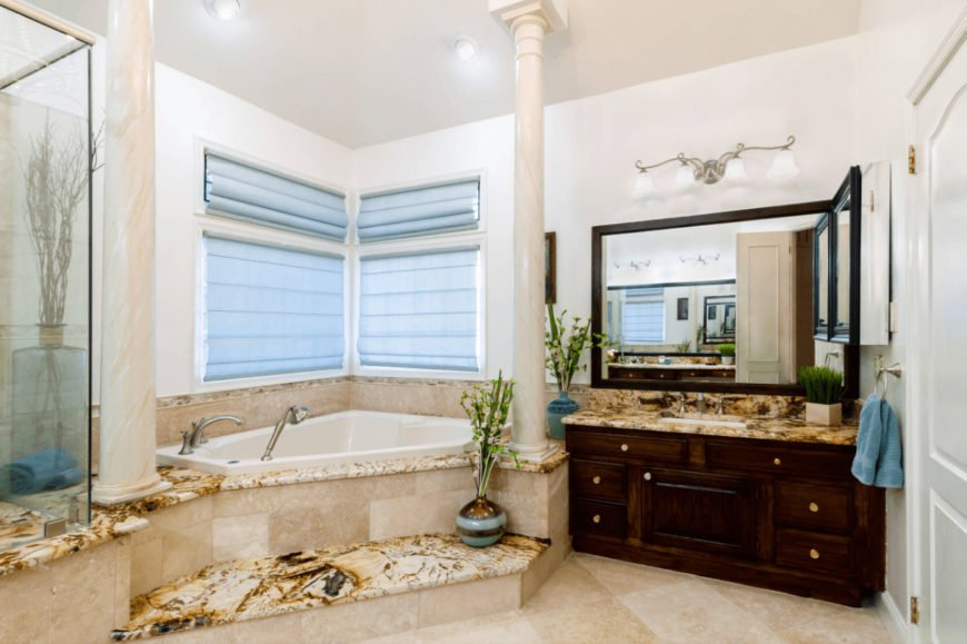 Mediterranean primary bathroom with tiled flooring and glazed windows covered in light blue roller blinds. It includes a dark wood vanity and corner tub lined with marble columns.