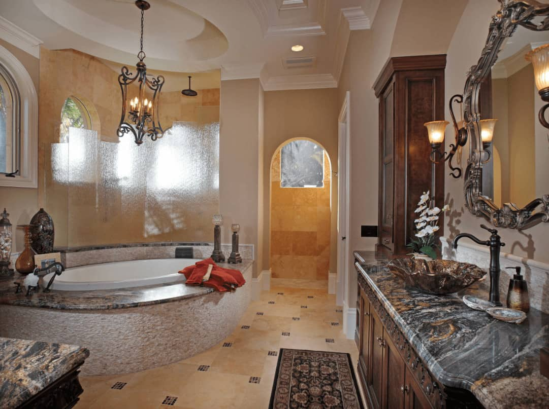 A gorgeous carved wood mirror hangs above the wooden vanity that's topped with vessel sink and wrought iron faucet. There's a drop-in tub across lighted by an ornate chandelier that hung from the oval tray ceiling.