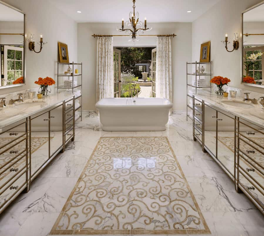 Fabulous primary bathroom with mirrored vanities and freestanding tub flanked by shelving units. It has white marble flooring designed with a lovely centerpiece along with a French door that opens to the yard.