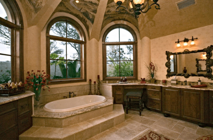 A green cushioned stool sits at a wooden sink vanity paired with a carved wood mirror. This room has limestone flooring and arched windows allowing natural light in.