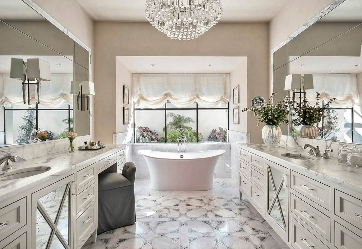 A fancy crystal chandelier adds class in this luxury primary bathroom with facing sink vanities and a freestanding tub by the framed window dressed in a charming roman shade.