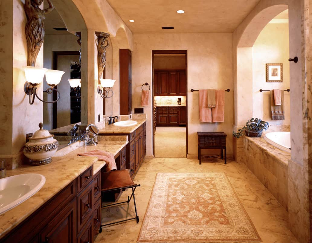 A classic area rug lays on the tiled flooring in this beige primary bathroom showcasing alcove bathtub and dual sink vanity with marble countertops and frameless mirrors.