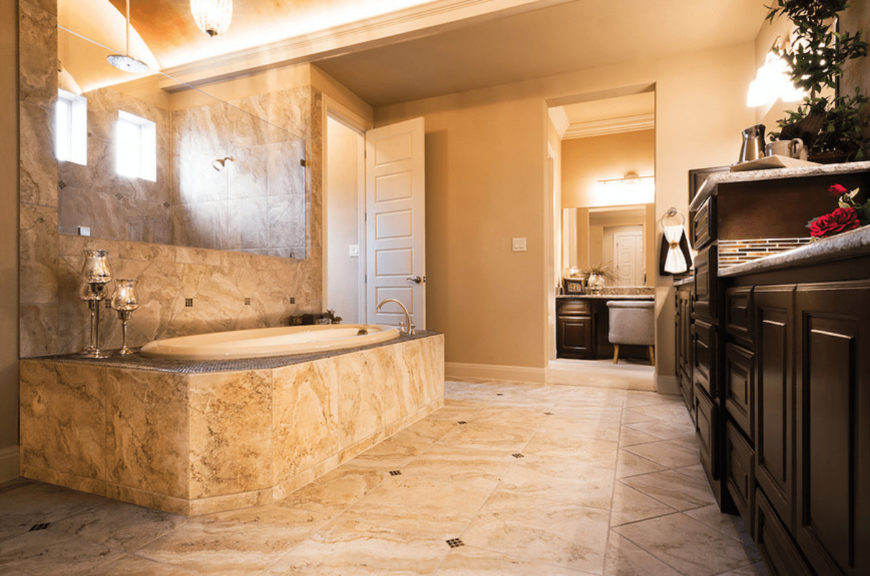 Beige primary bathroom with dark wood vanity and a drop-in tub placed beside the shower area. It is clad in elegant marble that blends in with the tiled flooring.