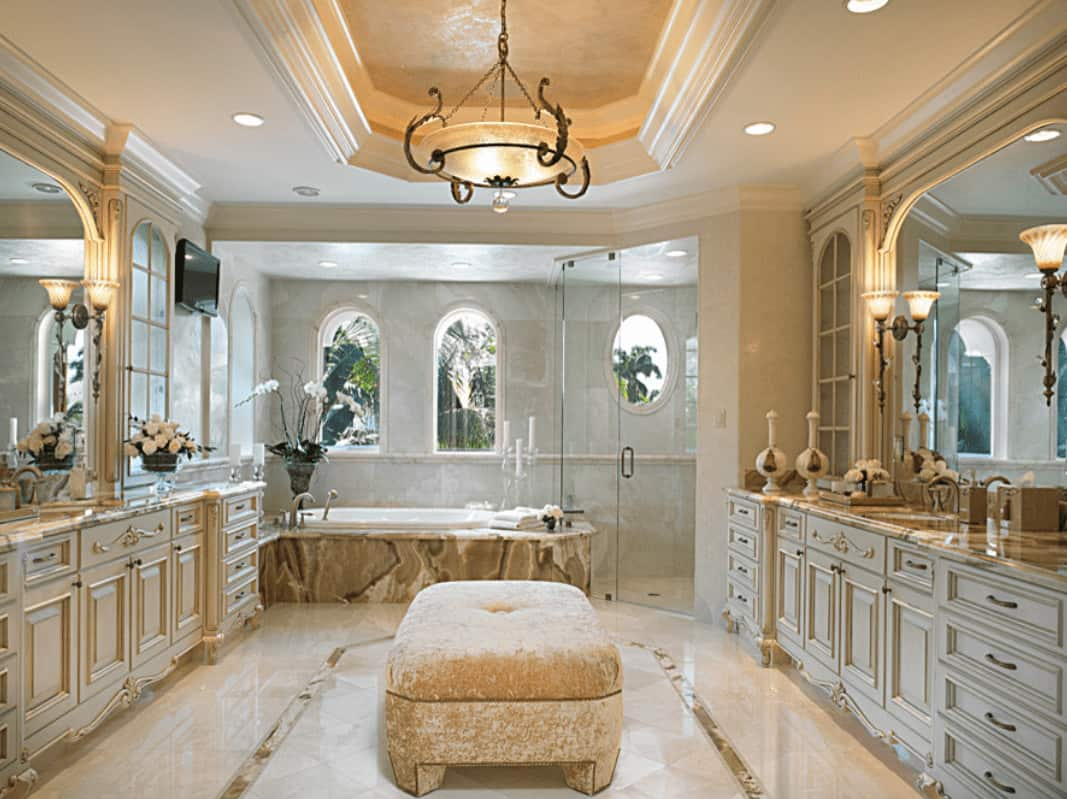 Classy marble tiles run throughout this primary bathroom with tray ceiling and arched windows bringing natural light in. It has a drop-in tub and facing vanities with a velvet ottoman in the middle.