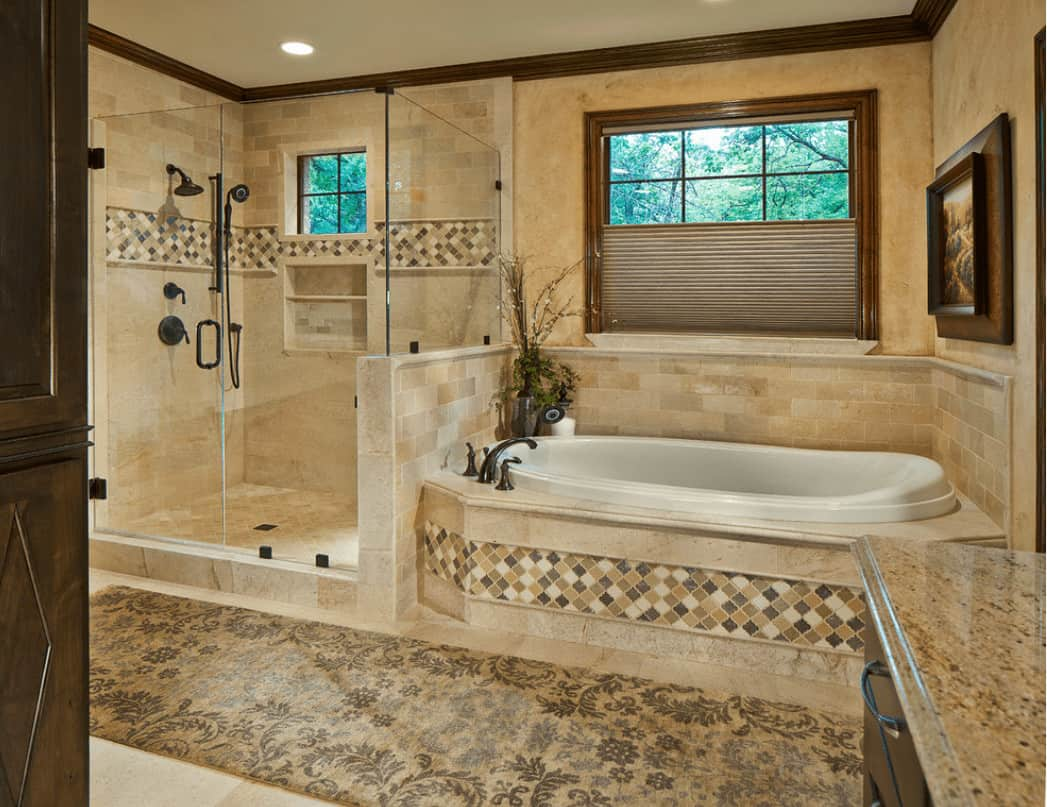 This primary bathroom showcases a deep soaking tub and walk-in shower with wrought iron fixtures. It includes wooden framed wall art and a floral runner that lays on the tiled flooring.