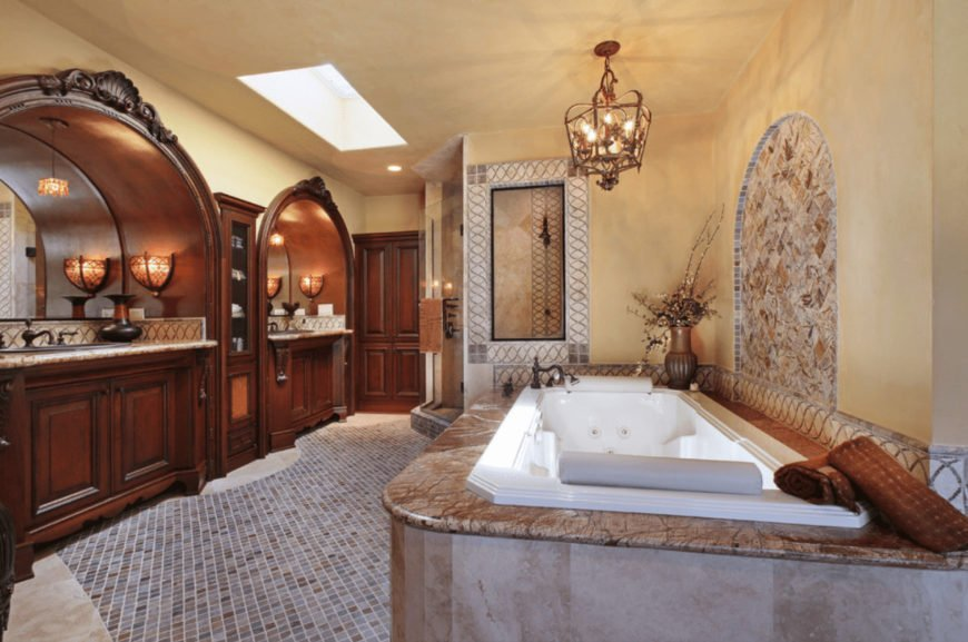 Sophisticated primary bathroom boasts alcove vanities with inset storage in the middle along with a drop-in tub lighted by a vintage chandelier. It has a regular beige ceiling fitted with skylight and marble flooring accented with mosaic tiles.