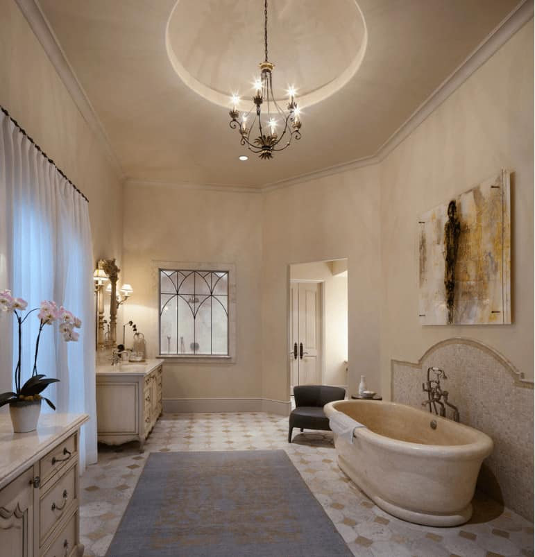 An interesting artwork hangs above the freestanding tub accompanied by a black leather chair. There are distressed nightstands across and an ornate chandelier that hung from the round tray ceiling.