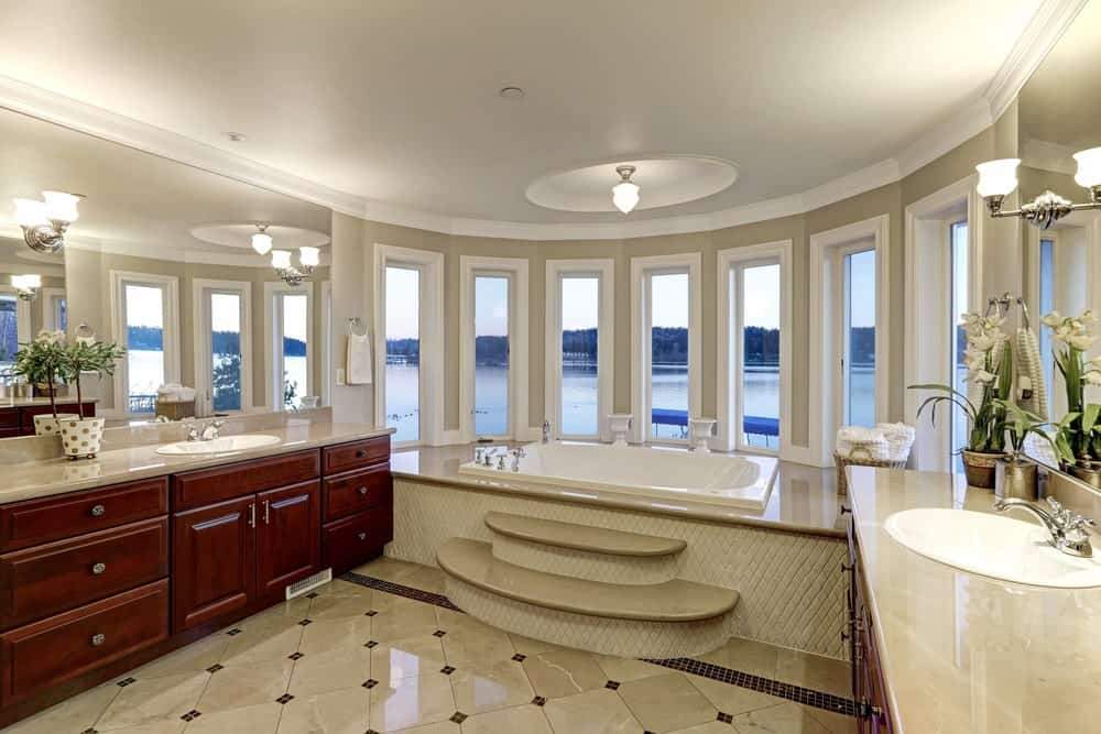This primary bathroom features redwood sink vanities with frameless mirrors on top mounted with chrome sconces. There's a drop-in tub by the glass paneled windows overlooking the serene outdoor view.