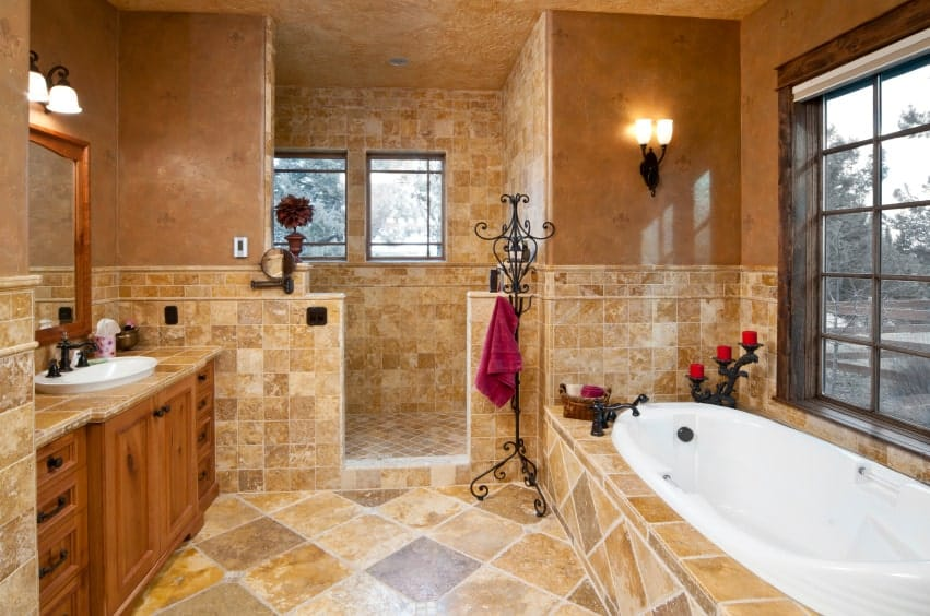 A wrought iron towel rack sits next to the deep soaking tub that's placed across the wooden sink vanity paired with a framed mirror. This room is illuminated by wall sconces and natural light from the glazed windows.