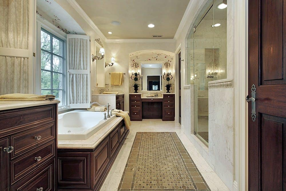 Fresh primary bathroom boasts dark wood vanities that complement the soaking bathtub placed beneath the white framed window. It has marble walls that extend to the flooring accented with bordered hex tiles.