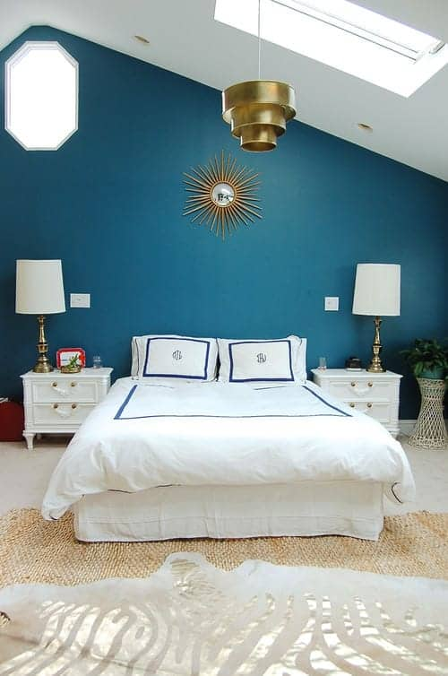 Gorgeous primary bedroom decorated with layered rugs and a sunburst mirror mounted above the white skirted bed. It has carpet flooring and a vaulted ceiling fitted with a skylight.