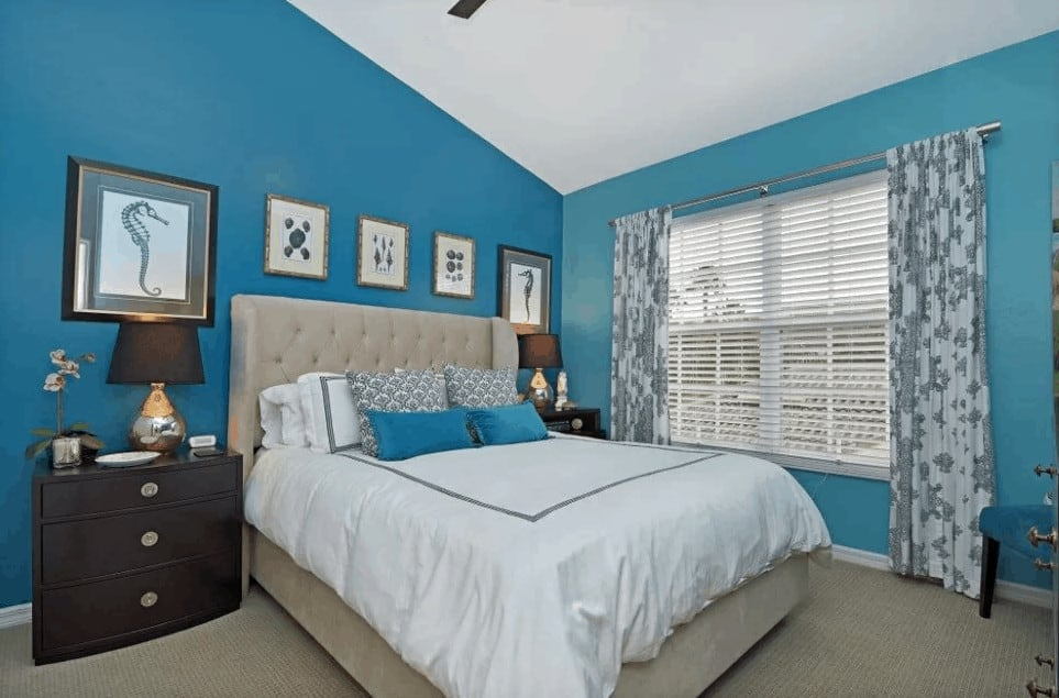 This primary bedroom features a tufted wingback bed in between wooden nightstands lined with framed wall arts. It has carpet flooring and glazed windows covered in floral draperies.