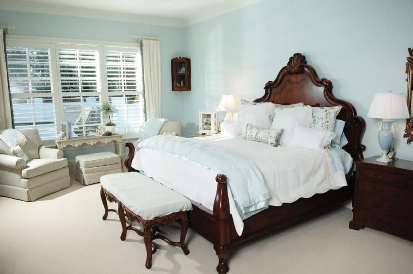Lovely table lamps sit on the dark wood nightstands in this primary bedroom with gray skirted chairs and a carved wood bed with a cushioned bench on its end.