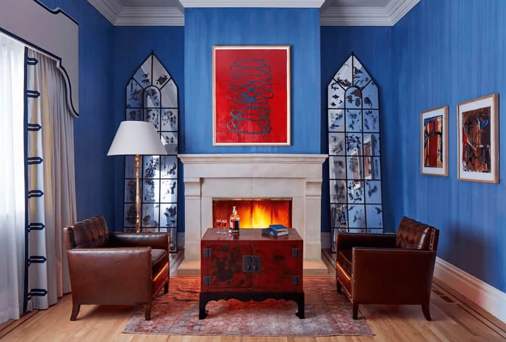 A red artwork stands out against the blue walls lined with white base and crown moldings. It has leather tufted armchairs and a wooden coffee table facing the fireplace flanked by stylish mirrors.