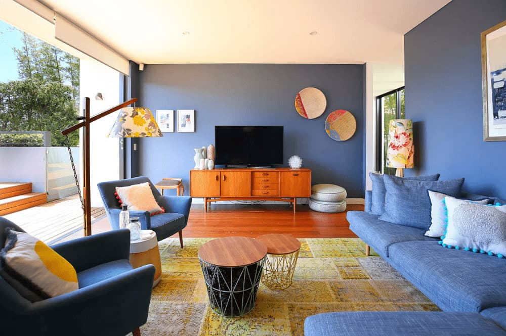 Blue armchairs and sectional surround a modular coffee table that sits on a yellow area rug. This room has lovely wall arts and a flat-screen TV on a wooden console blending in with the hardwood flooring.