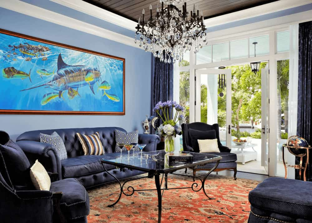 A large fish painting hangs over the leather tufted sofa facing the glass top coffee table over a red area rug. It is illuminated by a glam candle chandelier that hung from the tray ceiling clad in wood planks.