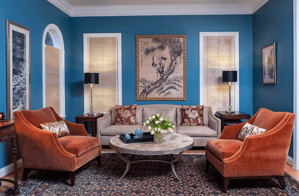 Traditional living room decorated with lovely artworks mounted on the blue walls. It has orange velvet chairs and ataupe sectional paired with a round coffee table that sits on a patterned rug.