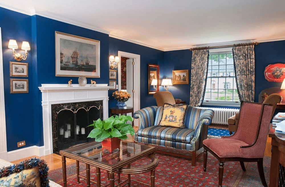This living room is designed with a mirror and gallery frames mounted on the royal blue walls. It has mismatched seats and a fireplace enclosed in a four-panel screen.