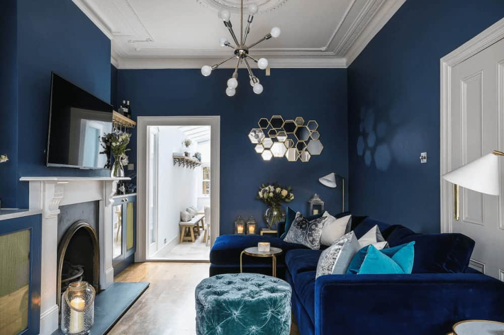 Blue living room decorated with cluster mirror and a contemporary chandelier that hung over the round tufted ottoman. It has an L-shaped sofa and an arched fireplace with a wall mount TV on top.