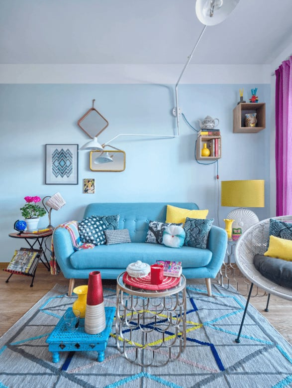 Round side tables flank a modern blue sofa paired with a stylish coffee table that sits on a textured rug. It is accompanied by floating shelves and a round chair filled with fluffy pillows.