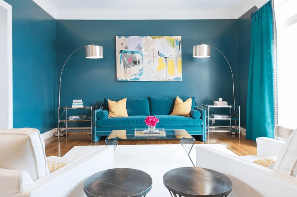 An abstract painting hangs over the blue sofa that blends in with the walls and drapes. It is flanked by metal side tables and chrome floor lamps with drum shades.