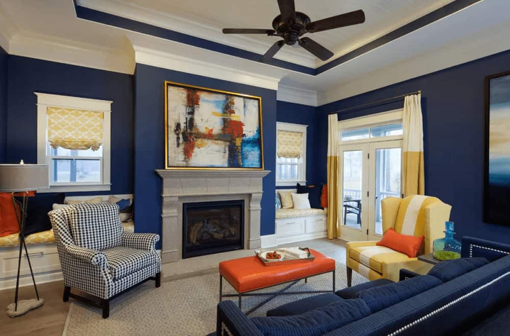 Blue living room with subtle yellow and orange accents from the drapes and valances along with wingback armchair and cushioned coffee table. It has a sectional sofa and a fireplace with gorgeous artwork on top.