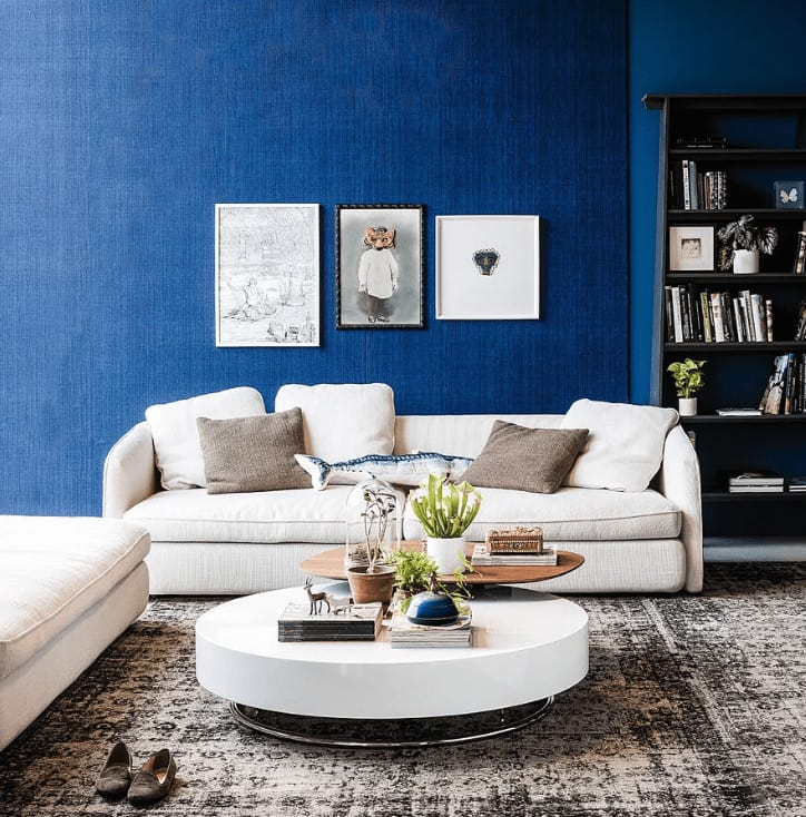 Interesting wall arts hang above the beige sofa paired with a round coffee table over a distressed area rug. It includes black shelving fitted against the blue wall.