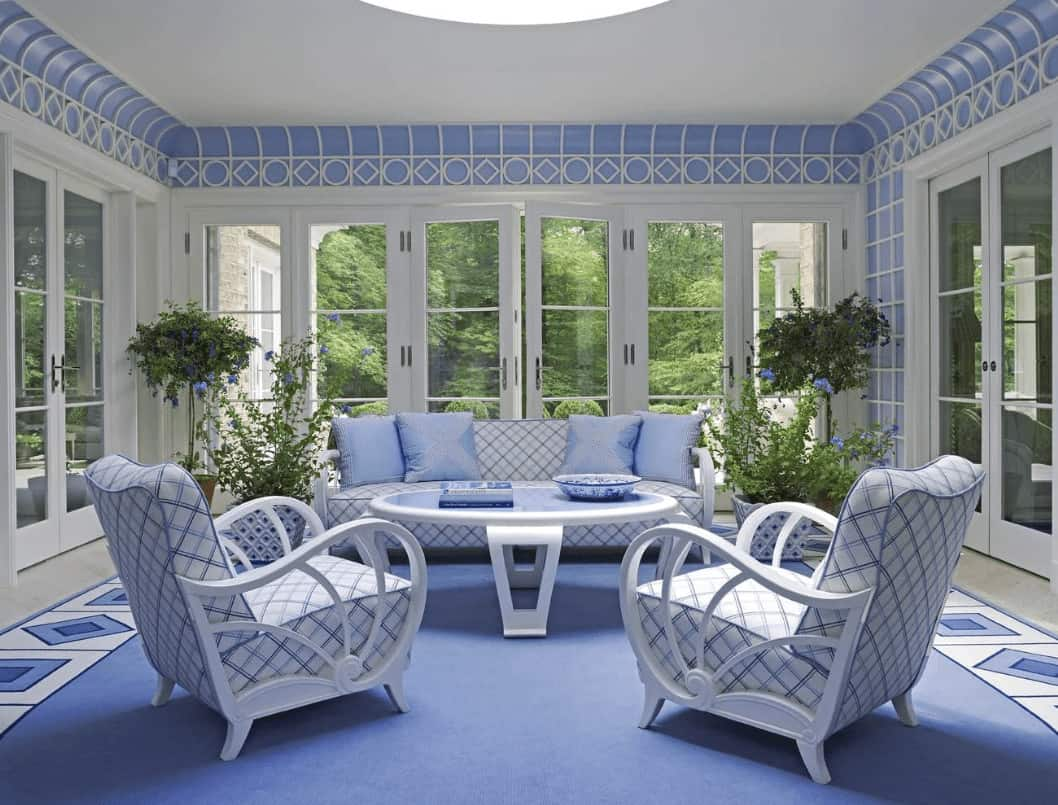 This living room is furnished with a round coffee table and patterned seats that harmoniously blend with the flooring and stylish ceiling. It has potted plants and French doors that open to the lush green yard.