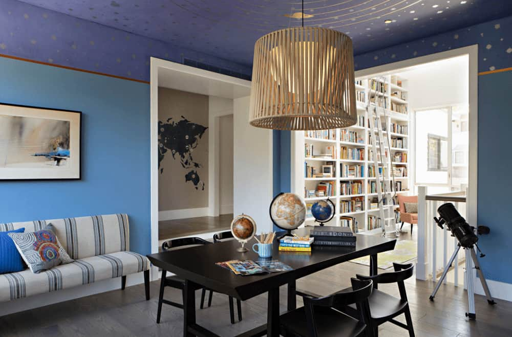 Blue living room boasts a striped sofa and a dark wood table with matching chairs over the natural hardwood flooring. It is lighted by an oversized pendant that hung from the solar system ceiling.