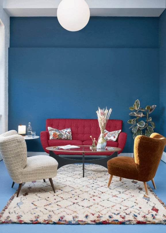 This living room is furnished with mismatched seats and a glass top coffee table illuminated by a round pendant light. It has blue walls and flooring topped by a charming area rug.