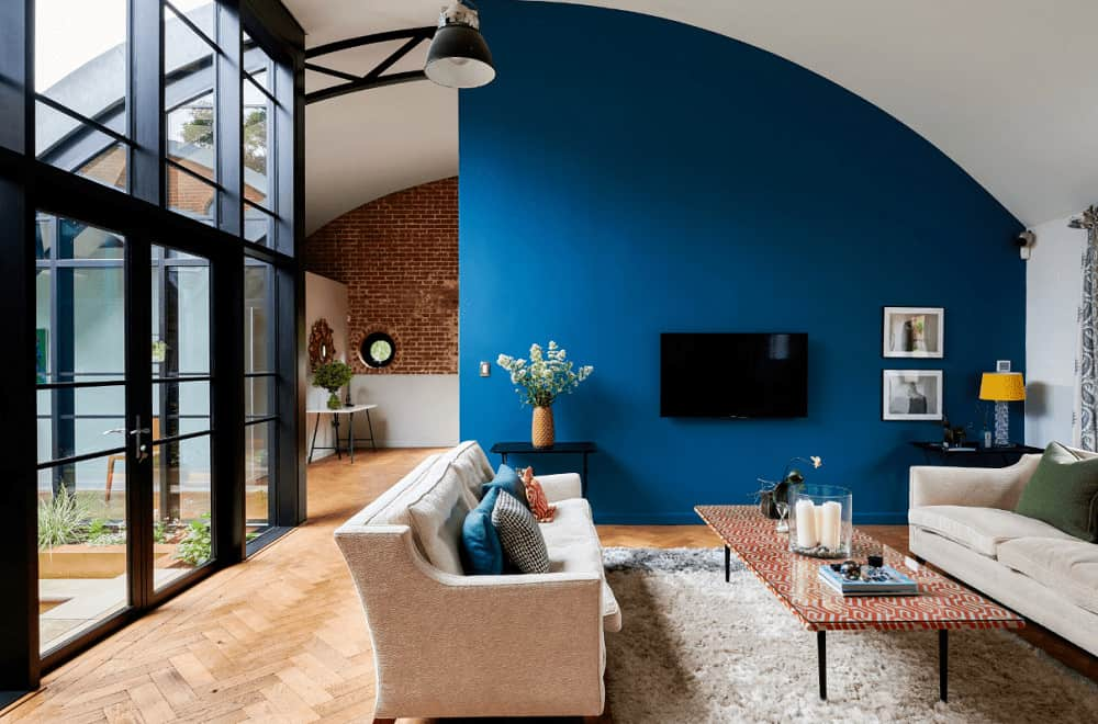Contemporary living room with arched ceiling and herringbone wood flooring topped by a shaggy rug. It includes beige sectional sofas with a patterned coffee table facing the wall mount TV.