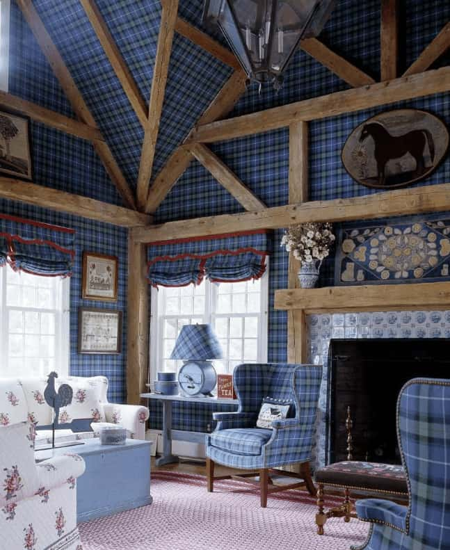 Clad in plaid wallpaper that matches the wingback chairs, this living room offers floral sofas and a fireplace framed in decorative tile surround. It has exposed wood beams adding a rustic touch to the charming room.