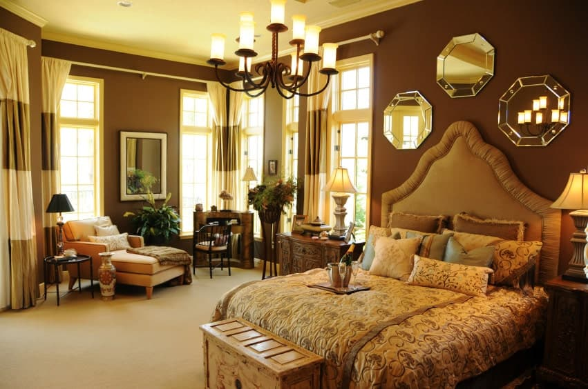 Brown primary bedroom offers a beige chaise lounge and upholstered bed with a wooden bench on its end. It is decorated with a wrought iron chandelier and octagonal mirrors.