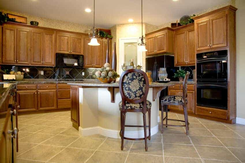 Black appliances complement the diamond pattern backsplash flanked by wooden cabinets. There's a granite top island in the middle accompanied by glass <a class=