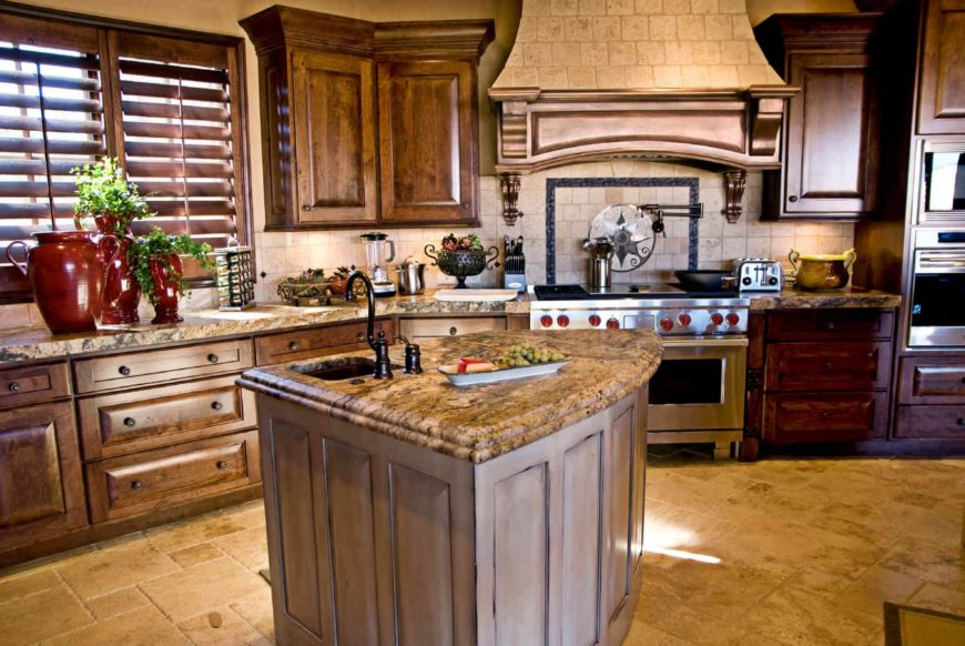 A brick range hood matches the backsplash that's accented with border tiles. It is accompanied by wooden cabinetry and a granite top island fitted with an undermount sink and wrought iron fixtures.