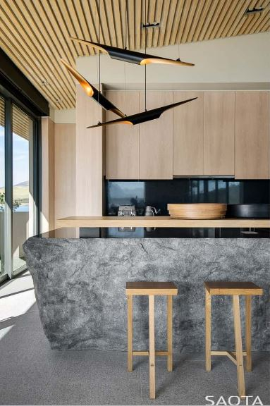 Wooden barstools sit at a boulder island with a raised wooden counter matching with the light wood cabinets that are contrasted by black granite backsplash. It is lighted by contemporary pendants that hung from the wood plank ceiling.