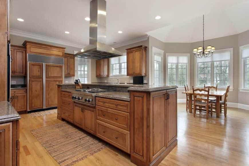 Airy kitchen with wooden cabinetry and a matching two-tier island fitted with a built-in cooktop. There's cozy dining set by the white framed windows lighted by a wrought iron chandelier.