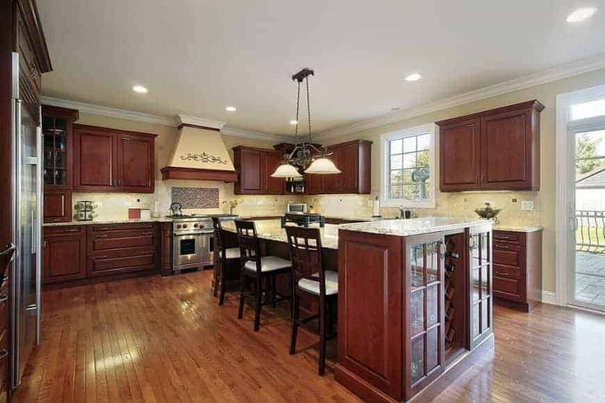 Glass pendant lights illuminate the granite top island attached with a wooden cabinet. It is surrounded by stainless steel appliances and wooden cabinetry against the beige walls.