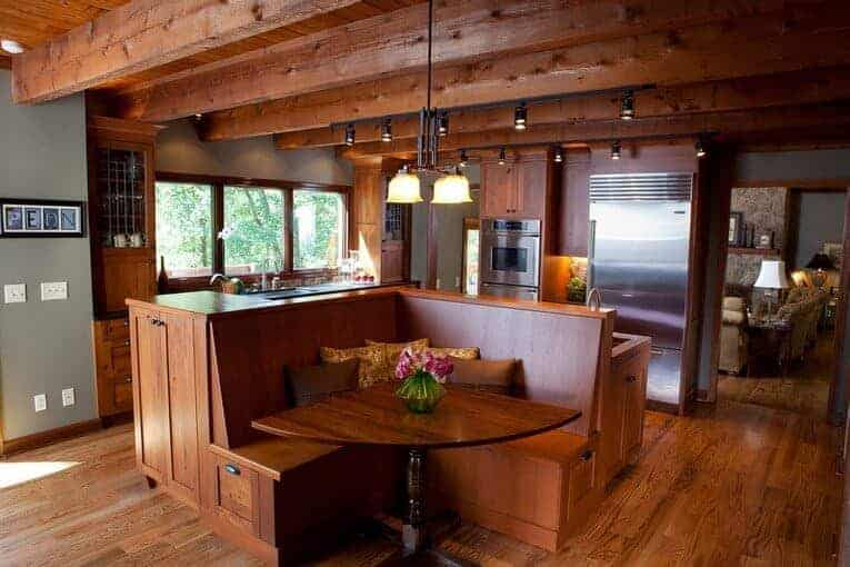 An eat-in kitchen with hardwood flooring and wood beam ceiling mounted with track lights and glass pendants. It includes wooden cabinetry and a matching island attached with a breakfast nook.