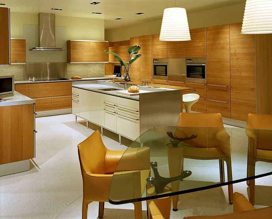 An eat-in kitchen with dome pendant lights and a glass top dining table surrounded by yellow leather chairs that complement the wooden cabinetry. It includes stainless steel appliances and two islands with quartz countertops.