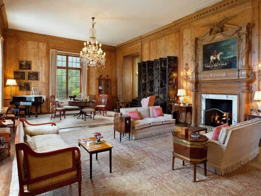 Large formal living room boasting a nice pair of couches set near the fireplace. There is also has a piano in the corner. The room is lighted by a glamorous chandelier.