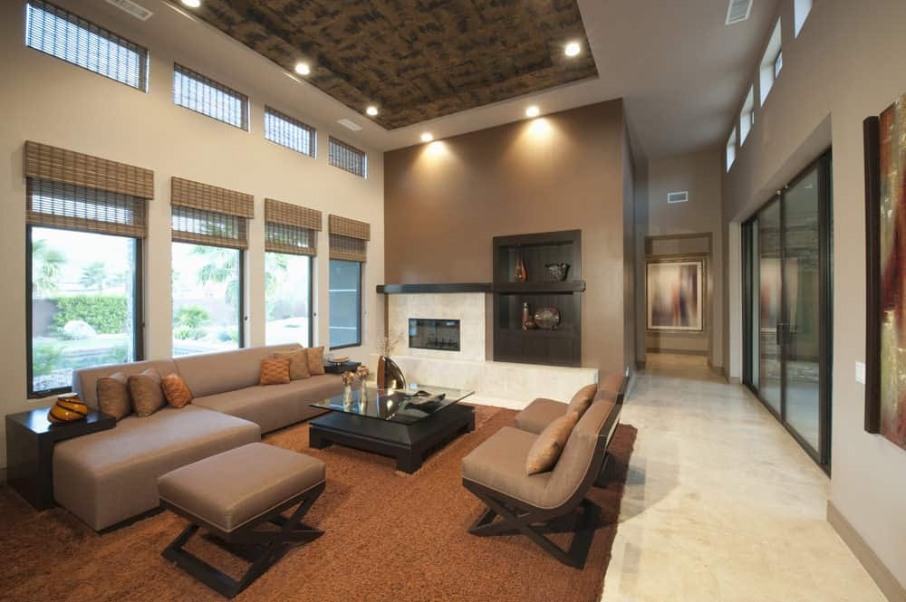 Large formal living space with a brown sofa set and a stylish tray ceiling. The room also offers a fireplace and a brown area rug.