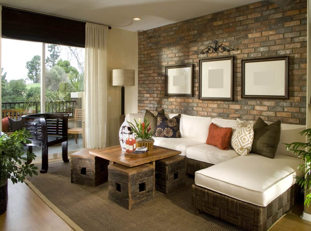 A focused look at this formal living room's stylish sofa set and center tables on top of the brown area rug. The brick wall features framed wall decors.