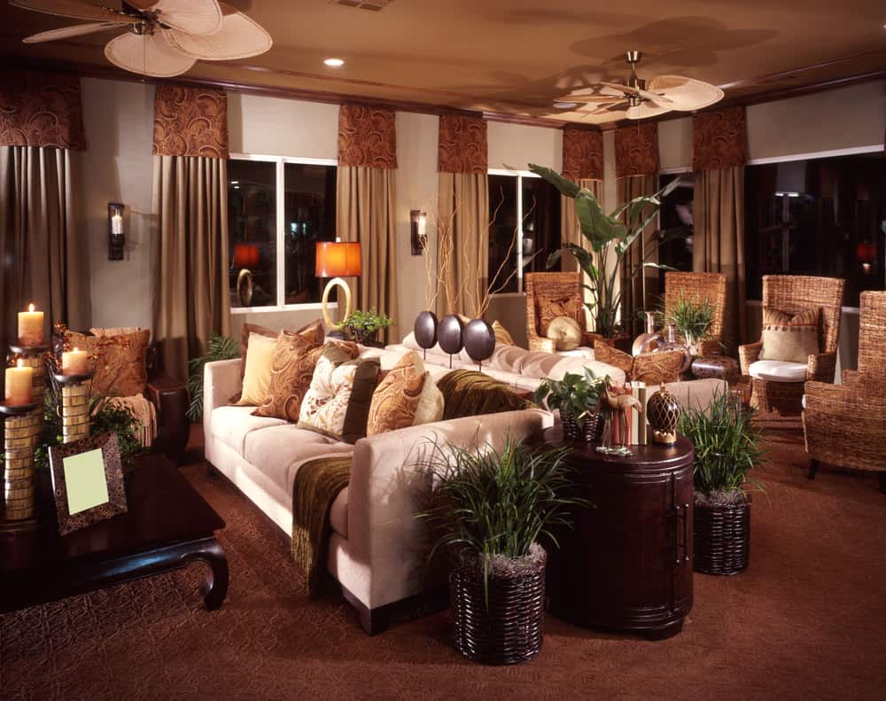 Large formal living room boasting a set of classy seats situated on the room's brown carpet flooring. The glass windows feature elegant brown window curtains.